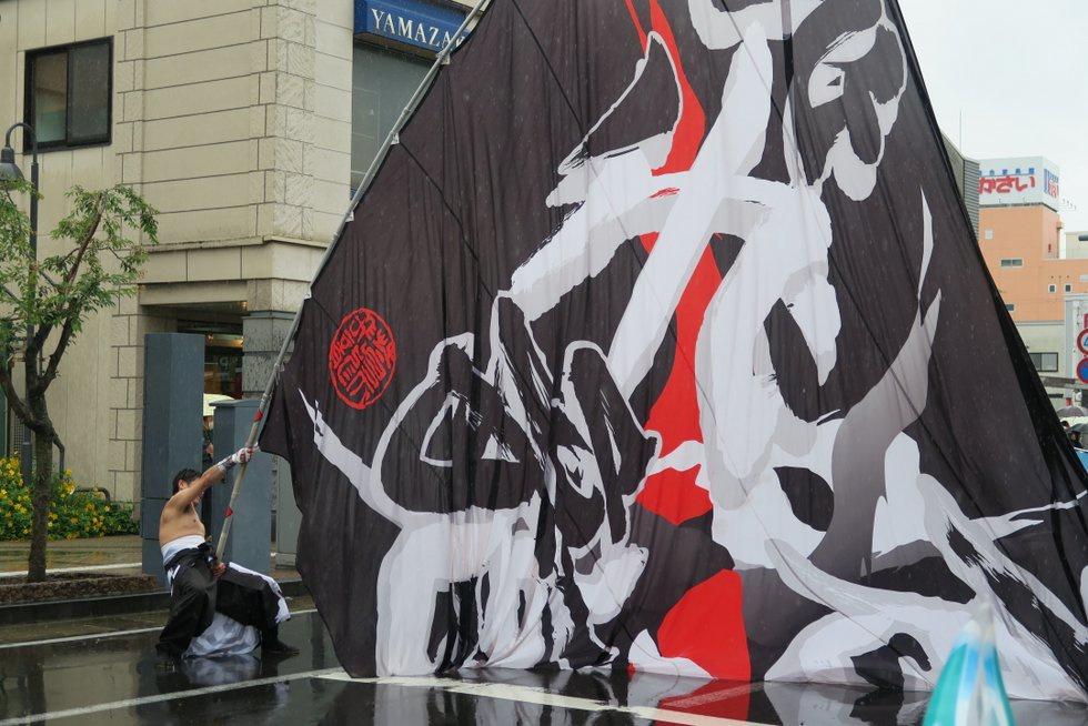 青森市の「蒼天飛龍」、濡れた大旗を振る筋力にみとれる