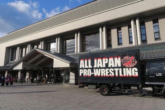青森県武道館とその前に止まる全日のトラック