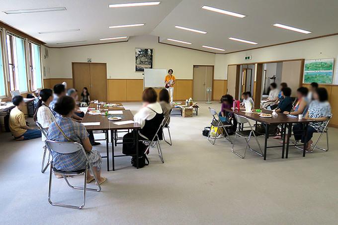 集会室で挨拶する斎藤(写真中央)