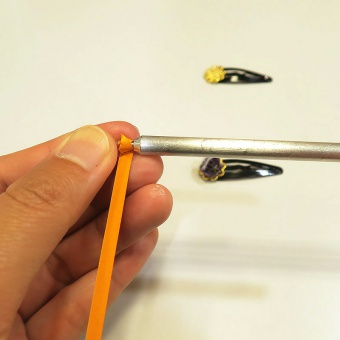 テープ状の紙を専用の棒に巻きつけていく