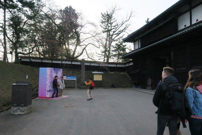 追手門前の桜ミクパネルの前で記念撮影する観光客